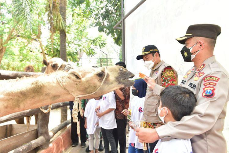 Kapolres Lamongan AKBP Miko Indrayana (kanan) dan Bupati Lamongan Yuhronur Efendi, bersama dengan anak yatim piatu korban Covid-19 di Lamongan ketika memberi makanan pada satwa di Mazoola, Jumat (17/9/2021).