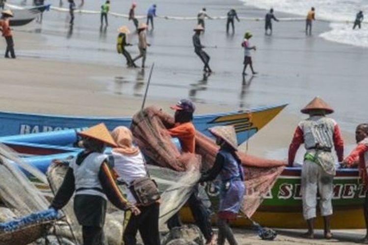 Nelayan tradisional menarik tambang jaring ered di pesisir Pantai Timur, Kabupaten Pangandaran, Jawa Barat, Minggu (27/10/2019).