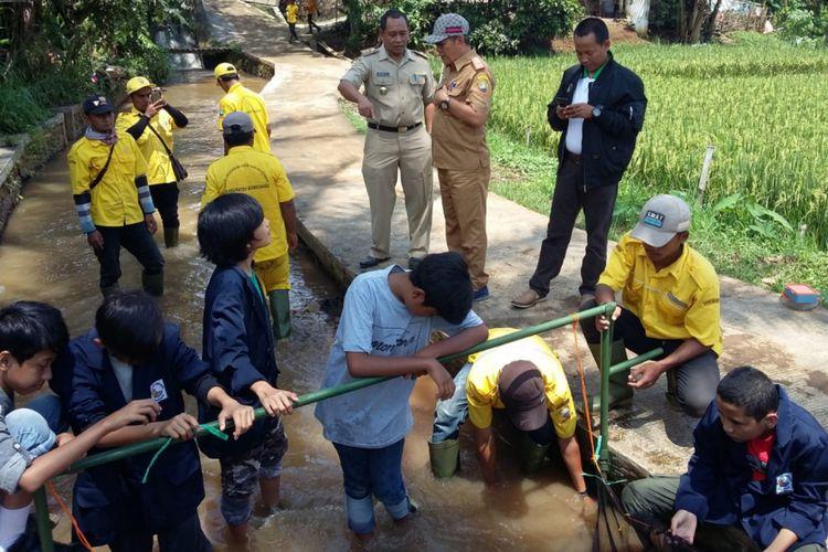 Pelajar Internasional Green School bersama tim URC DLHK Sumedang memasang jaring penahan sampah untuk mengatasi masalah banjir yang kerap merendam Jalan Kutamaya, Kompleks Islamic Center Sumedang, Selasa (26/2/2019).