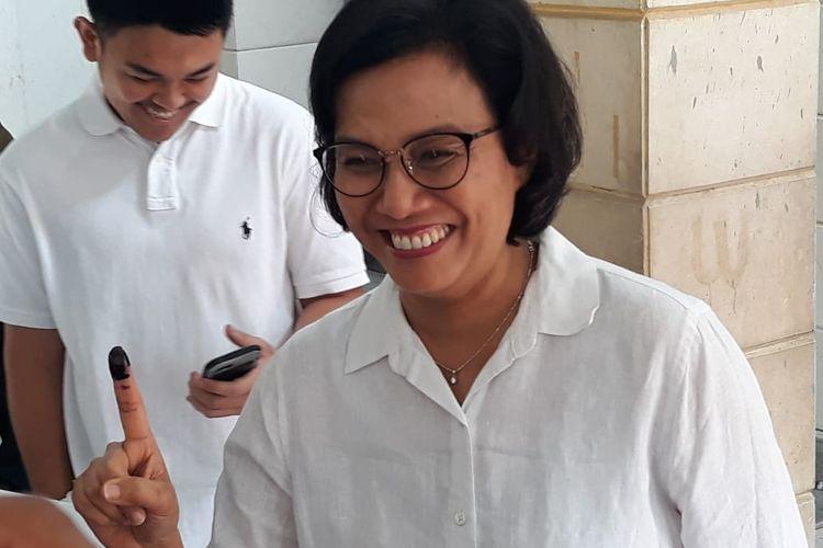 Menteri Keuangan Sri Mulyani menunjukkan jari telunjuk tangan kanannya yang telah dibasahi tinta tanda usai memberikan suaranya di TPS 77, Jalan Mandar, Kelurahan Pondok Karya, Kecamatan Pondok Aren, Tangerang Selatan.