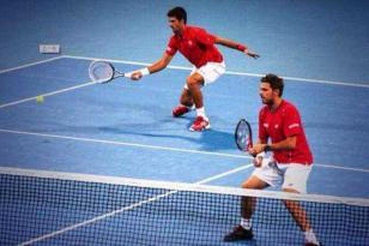 Petenis Serbia, Novak Djokovic (kiri) bersiap mengembalikan bola saat berpasangan dengan Stanislas Wawrinka dari Swiss. Mereka menang atas Mahesh Bhupati/Robert Lindstedt pada babak pertama China Open, yang berlangsung di Beijing, Selasa (1/10/2013).