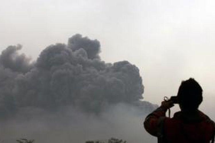 Warga memotret erupsi Gunung Kelud dari Kota Kediri, Jawa Timur, 14 Februari 2014. Erupsi gunung ini mengakibatkan hujan abu dan kerikin yang menutupi banyak wilayah di Jawa Timur dan Jawa Tengah. Ribuan orang mengungsi.