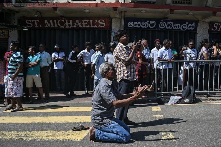 Warga Sri Lanka berdoa di luar gereja St Anthony di Kolombo pada Senin (22/4/2019), sehari seteah tempat ibadah itu diguncang serangan bom.