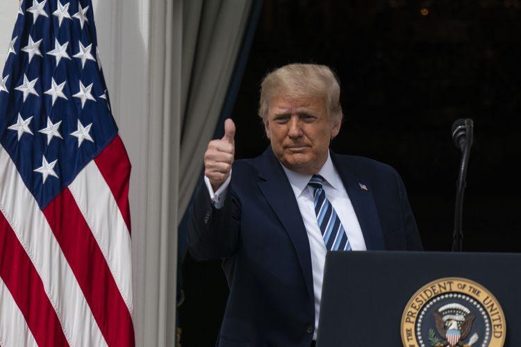 Presiden Amerika Serikat Donald Trump mengacungkan jempol saat beranjak meninggalkan Blue Room Balcony Gedung Putih. Ia menyapa para pendukungnya pada Sabtu (10/10/2020).