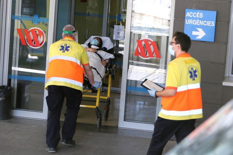 Seorang perempuan dibawa menggunakan brankar di Rumah Sakit Arnau de Vilanova, setelah pemerintah Catalonia menerapkan larangan baru dalam rangka menangkal wabah virus corona di Lleida, Spanyol, pada 4 Juli 2020.