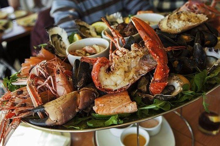 Ilustrasi seafood platter, ada udang, lobster, kepiting, kerang dalam satu piring.