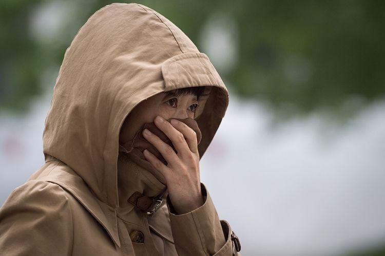 Warga menutupi hidung untuk melindungi diri dari kualitas udara yang buruk akibat badai pasir di Beijing, China, Kamis (4/5/2017). Badai pasir menerjang sebagian besar wilayah China Utara termasuk Beijing yang menyebabkan angin dipenuhi debu dan menghalangi daya pandang.