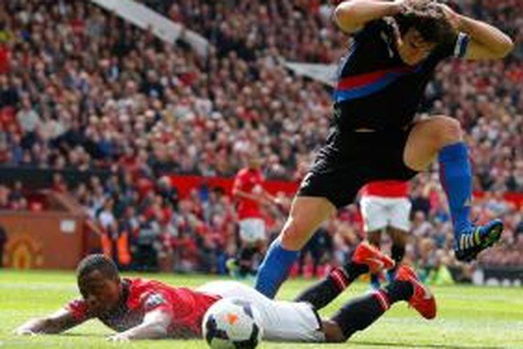Bek Manchester United, Patrice Evra, dijatuhkan salah satu pemain Crystal Palace saat kedua tim bertemu dalam lanjutan Premier League, Sabtu (14/9/2013).