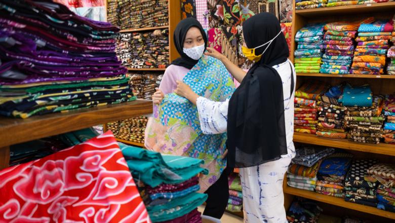 Pembeli sedang mengamati motif dan bahan kain di toko.