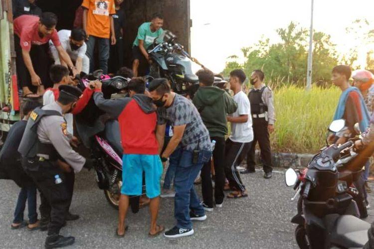 Petugas kepolisian Polsek Tampan dan Polresta Pekanbaru saat mengangkut 32 unit sepeda motor pelaku balap liar yang diamankan di Stadion Utama Riau Jalan Naga Sakti, Kecamatan Tampan, Pekanbaru, Riau, Minggu (19/7/2020) sore.