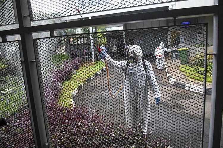 Petugas menyemprotkan cairan disinfektan di pintu masuk rumah tahanan KPK di Jakarta, Rabu (18/3/2020). Untuk mencegah penyebaran COVID-19, KPK melakukan disinfeksi di sejumlah area Gedung Merah Putih.
