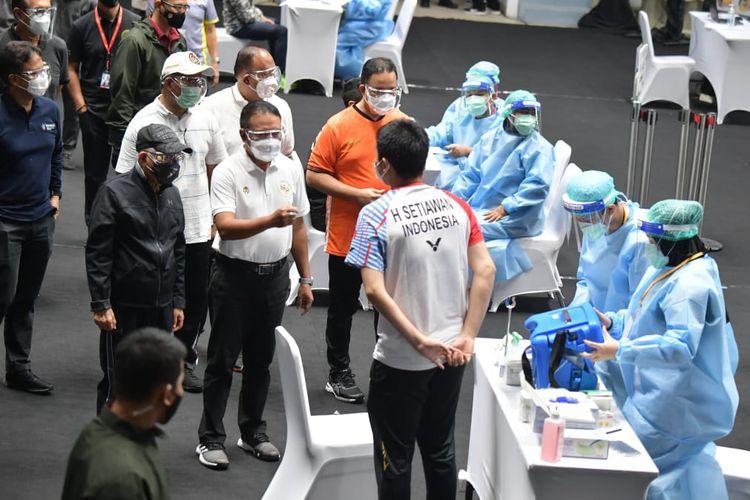 Menpora Zainudin Amali dan Wakil Presiden Ma'ruf Amin menyapa atlet bulu tangkis Indonesia, Hendra Setiawan, saat acara pemberian vaksin bagi atlet di Istora Senayan, Jakarta, Jumat (26/2/2021).