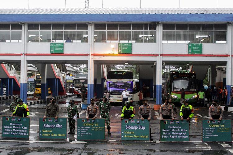 Petugas gabungan membawa poster himbauan penerapan 5M protokol kesehatan di Terminaal Purabaya, Bungurasih, Sidoarjo, Jawa Timur, Kamis (4/2/2021). Sosialisasikan penerapan 5M protokol kesehatan di kawasan terminal dalam pelaksanaan Pembatasan Kegiatan Masyarakat (PPKM) tersebut dilaksanakan Polda Jatim dan Pangdam V Brawijaya bersama Forkopimda Sidoarjo dengan membagikan masker dan sembako kepada penumpang dan kru bus. ANTARA FOTO/Umarul Faruq/rwa.
