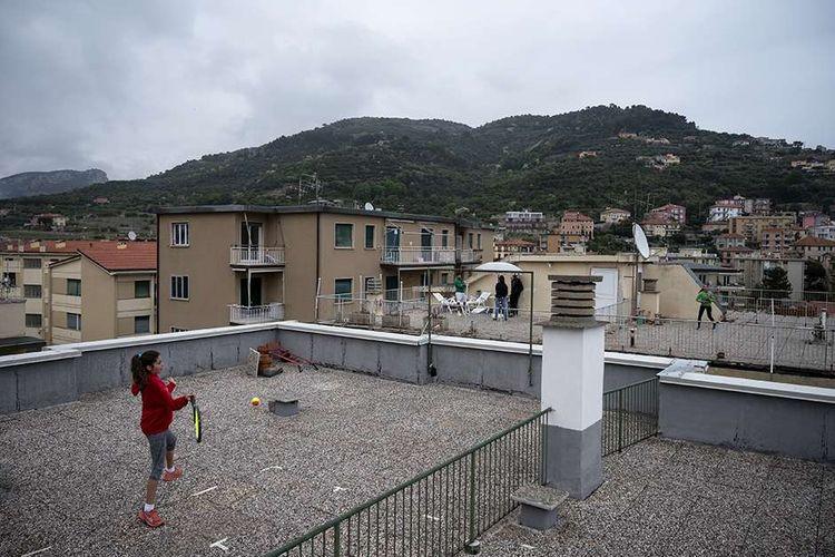 Carola Pessina (kiri) bermain tenis dengan Vittoria Oliveri di atas atap rumah mereka di Finale Ligure, wilayah Liguria, Italia, selama diberlakukan karantina nasional (lockdown), Minggu (19/4/2020). Rasa jenuh selama masa karantina pencegahan virus corona, menjadikan area atap rumah atau apartemen banyak difungsikan warga sebagai alternatif lokasi berkegiatan.