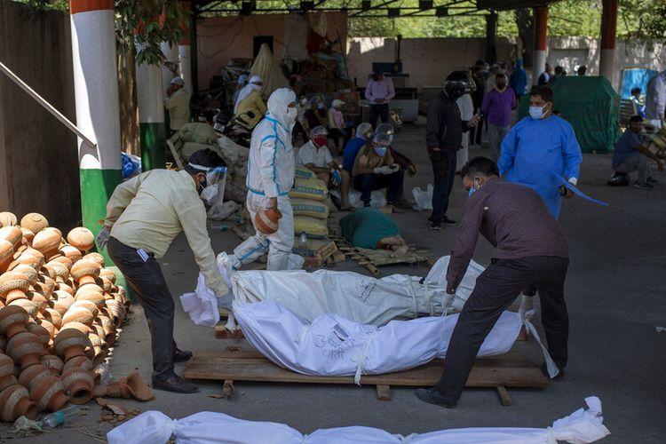 Orang-orang menyusun mayat korban meninggal karena Covid-19 di sebuah krematorium, di New Delhi, India, Sabtu, 24 April 2021