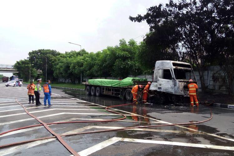 Petugas berhasil memadamkan api yang membakar truk di tepi jalan tol.