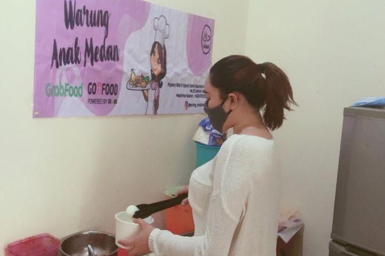Nelam Sari Tanjung Menyiapkan Pesananan Makanan