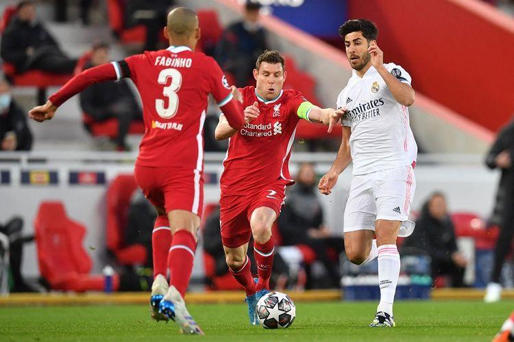 Gelandang Liverpool Fabinho (kiri) dan rekan setim James Milner (tengah) bersaing dengan gelandang Real Madrid Marco Asensio dalam pertandingan leg kedua perempat final Liga Champions antara Liverpool vs Real Madrid di Anfield Liverpool pada 14 April 2021.