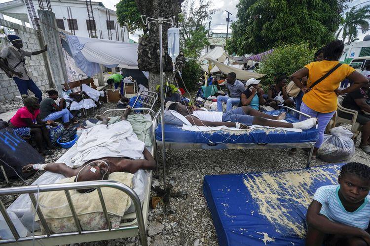 El lunes 16 de agosto de 2021, dos días después de un terremoto de magnitud 7,2 en el suroeste del país, un hombre herido yacía en una cama frente al Hospital de la Inmaculada Concepción en Les Case, Haití.