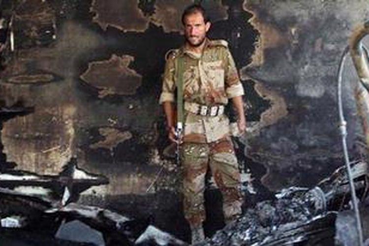 Seorang petugas keamanan Yaman memeriksa puing pesawat militer yang jatuh dekan Bandara Sanaa, Yaman dan menewaskan 10 orang penumpangnya.