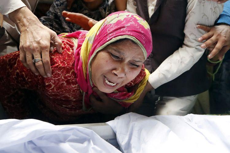 Seorang wanita menangisi anaknya, Hashim Ali, yang terluka saat bentrokan terjadi di New Delhi, India, Selasa (25/2/2020). Kerusuhan terjadi akibat UU Kewarganegaraan India yang kontroversial.