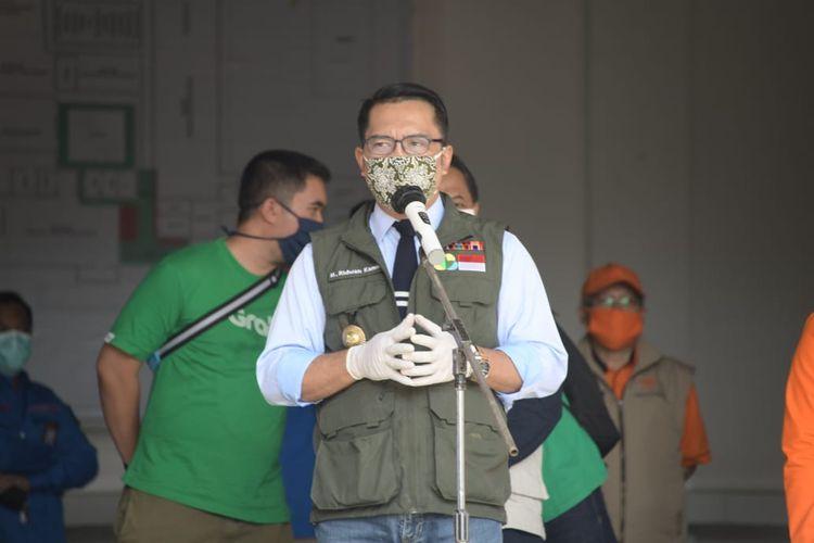 Gubernur Jawa Barat Ridwan Kamil saat melepas petugas pos dan ojek online (ojol) untuk menyalurkan bansos dari Pemprov Jabar kepada Keluarga Rumah Tangga Sasaran (KRTS) Kota Bandung di Kantor Sentral Pengolahan Pos (SPP) Bandung, Kota Bandung, Minggu (19/4/2020).