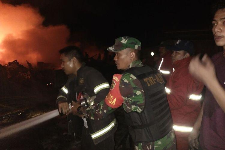 Petugas TNI dan damkar berupaya memadamkan api kebakaran ruko dan kios di Pasar SP 1 Desa Kijang Kaya, Kecamatan Tapung Hilir, Kabupaten Kampar, Riau, Selasa (9/3/2021) malam.