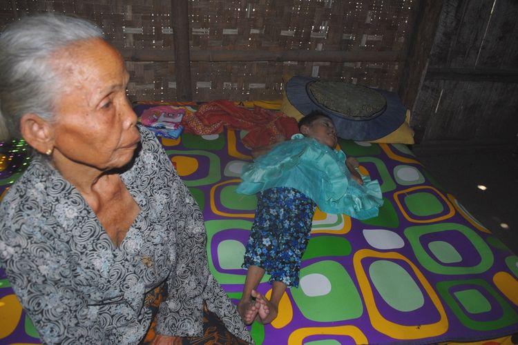Mbah Rani (75) merawat cucunya, Rosma (10) yang menderita lumpuh di rumahnya di Desa Nglobar, Kecamatan Purwodadi, Kabupaten Grobogan, Jawa Tengah, Sabtu (5/10/2019) siang.