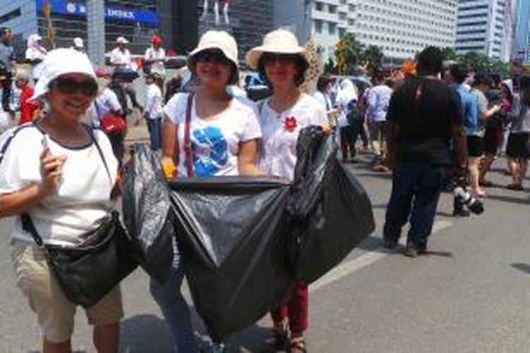 Tiga wanita ini melakukan aksi bersih sampah di Jalan MH Thamrin, saat perayaan pelantikan Joko Widodo dan Jusuf Kalla sebagai presiden dan wakil presiden. Senin (20/10/2014).