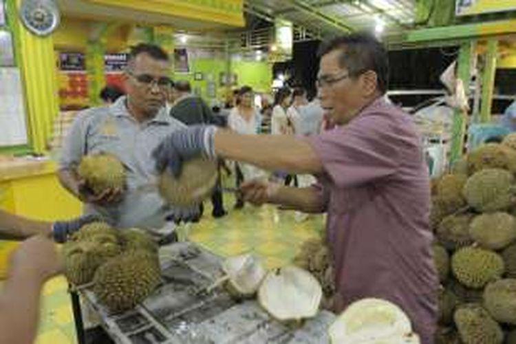 Zainal Abidin (baju merah) alias Ucok pemilik usaha Durian Ucok di Kota Medan, Sumatera Utara, sedang memilihkan durian pesanan pelanggan, Kamis (25/8/2016)