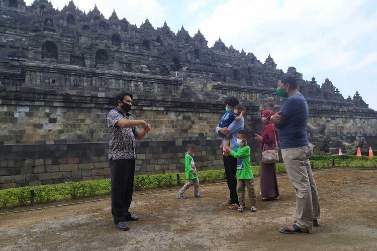 Pemandu wisata sedang menerangkan tentang Candi Borobudur kepada wisatawan di halaman zona I Candi Borobudur Magelang, Senin (7/7/2020).