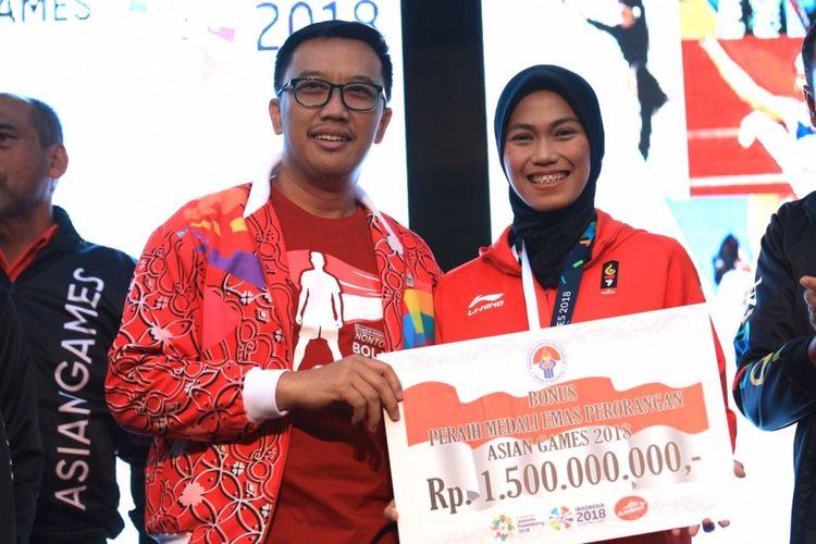 Menpora Imam Nahrawi menyerahkan secara simbolis bonus kepada atlet peraih medali emas Asian Games 2018, Defia Rosmaniar, di Kemenpora, 20 Agustus 2018.