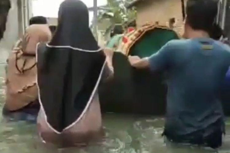 Video yang mendokumentasikan jenazah di dalam keranda diangkut di atas perahu dengan didorong sejumlah warga menerobos banjir di wilayah Kabupaten Kudus, Jawa Tengah viral di media sosial, Selasa (2/2/2021).