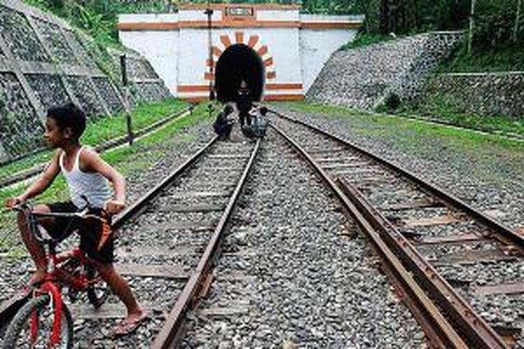 Sejumlah warga bermain di sekitar mulut terowongan jalur kereta api di Lampegan, Cibeber, Cianjur, Jawa Barat, jalur penghubung kereta api Cianjur Sukabumi, Senin (7/4/2014). Terowongan tertua di Indonesia dengan panjang 686 meter ini dibangun tahun 1879-1882 oleh Staats Spoorwegen, perusahaan kereta api masa Hindia Belanda.