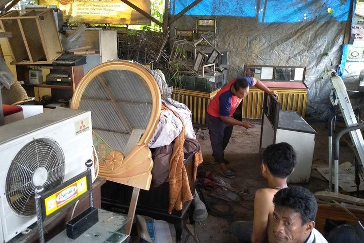 Wim sibuk membersihkan barang-barang di gudang di Jalan Sunan Kalijaga, Desa Manunggal, Kecamatan Helvetia, Deli Serdang. Di tempat ini pada Jumat sore digerebek oleh tim Densus 88 Anti Teror dan mengamankan 500 kotak amal, ratusan suker, baju dan lainnya.