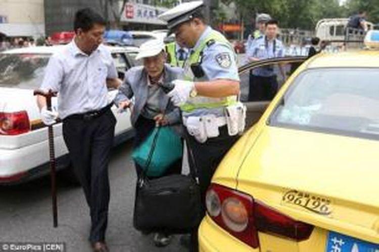 Akibat usianya yang lanjut, Wang Xia (86) harus dipapah seorang polisi dan sopirnya saat akan mengikuti ujian masuk perguruan tinggi.