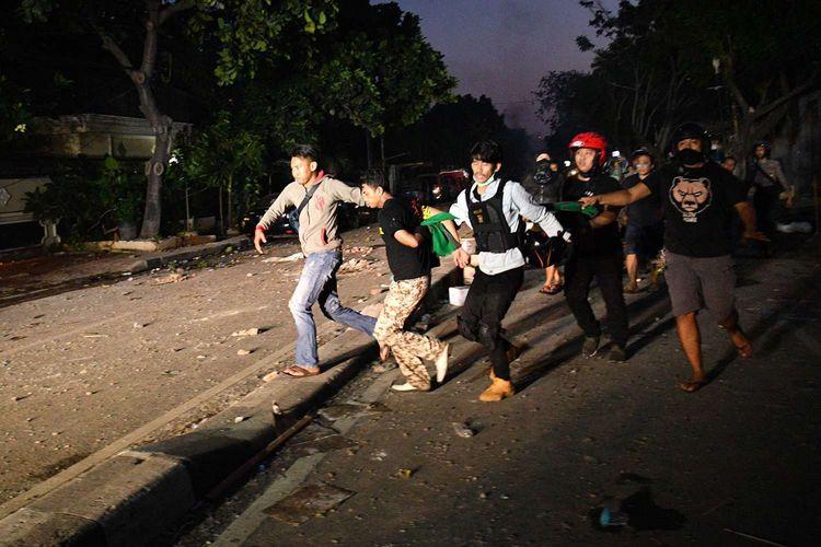 Polisi dan warga menangkap seorang yang diduga menjadi provokator pembakaran mobil di Komplek Asrama Brimob, Petamburan, Jakarta, Rabu (22/5/2019).