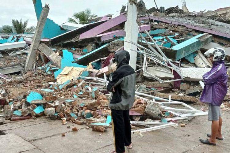 Warga mengamati bangunan RS Mitra Manakarra yang roboh pascagempa bumi, di Mamuju, Sulawesi Barat, Jumat (15/1/2021).