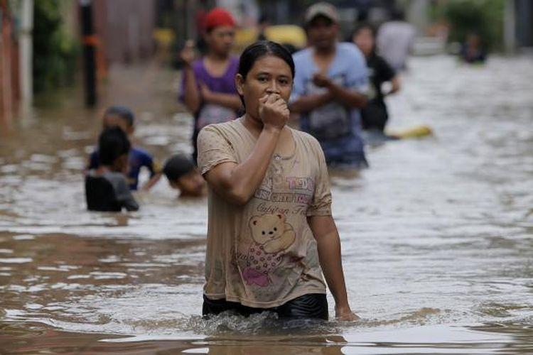 Warga berjalan menembus banjir di Kelurahan Cipinang Melayu, Kecamatan Makasar, Jakarta Timur, Senin (20/2/2017). Banjir kerap terjadi menyusul meluapnya Kali Sunter yang melintasi Cipinang Melayu, ditambah, curah hujan yang tinggi sepanjang hari kemarin.