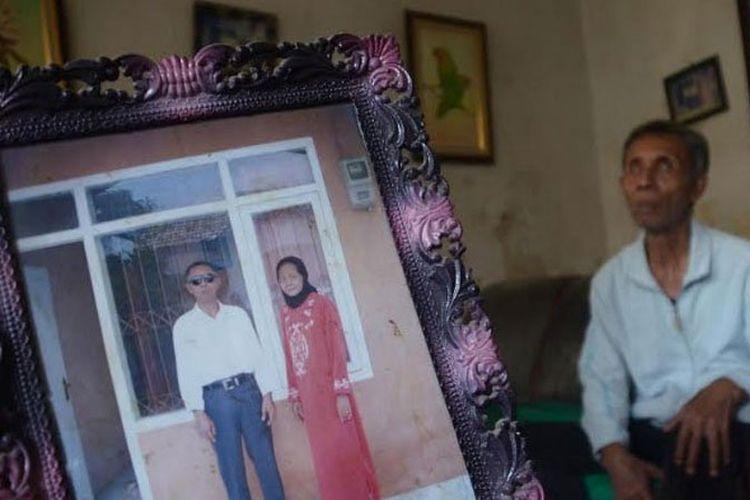 Soeharto, duduk di belakang bingkai foto yang menampilkan dirinya bersama sang istri di depan rumah pemberian pemerintah 2008 silam, karena dia adalah putra daerah Probolinggo dan memiliki prestasi di bidang olahraga.