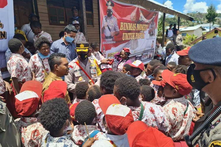 Binmas Noken Polda Papua dan Kapolres Intan Jaya AKBP Sandi Sultan tengah nercenkrama dengan siswa sekolah yabg ada di Distrik Sugapa, Papua, Rabu (24/3/2021)