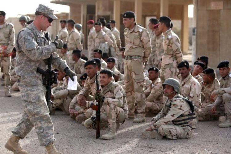 Seorang anggota militer Amerika Serikat memberikan jempol ke arah pasukan Irak di Kompleks Pangkalan Taji, dekat ibu kota Baghdad.