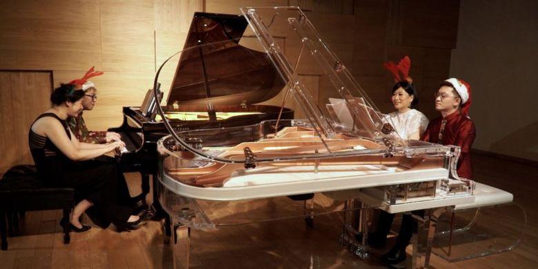 Empat pianis dengan dua piano membawakan lagu medley natal.