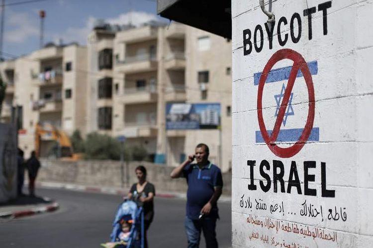 Warga Palestina berjalan di dekat sebuah tanda di tembok Bethlehem yang menyerukan untuk memboikot produk Israel.