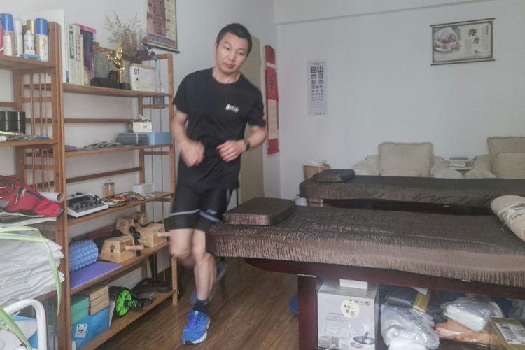 Pelari jarak jauh asal China berlari di dalam rumahnya sebagai bentuk perlawanan terhadap virus corona. (AFP)