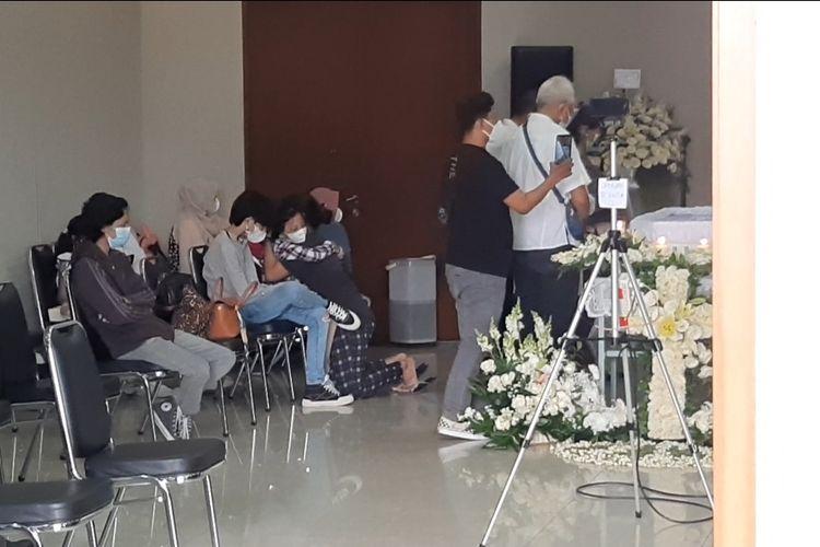 Putra Raditya Oloan, Zeraiah (berkemeja kotak-kotak) saat berada dekat peti Raditya Oloan disemayamkan di Rumah Duka RSPAD Gatot Subroto, Jumat (7/5/2021).