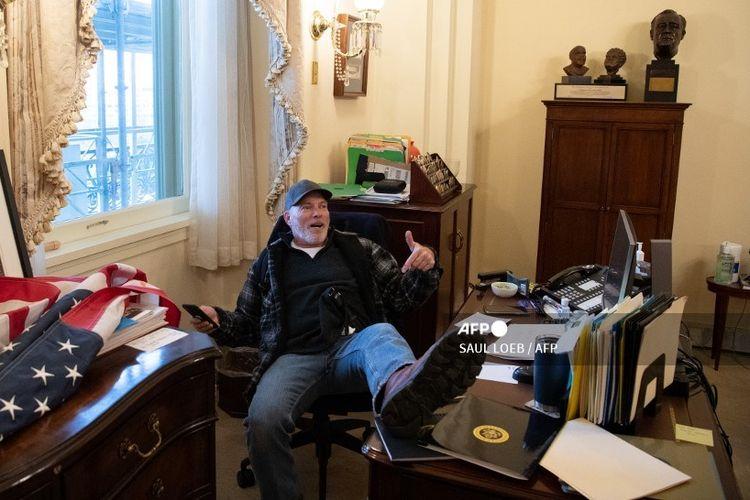 Richard Barnett, seorang pendukung Presiden AS Donald Trump duduk di dalam kantor Ketua DPR AS Nancy Pelosi saat menyerbu Gedung Capitol di Washington, DC, 6 Januari 2021.