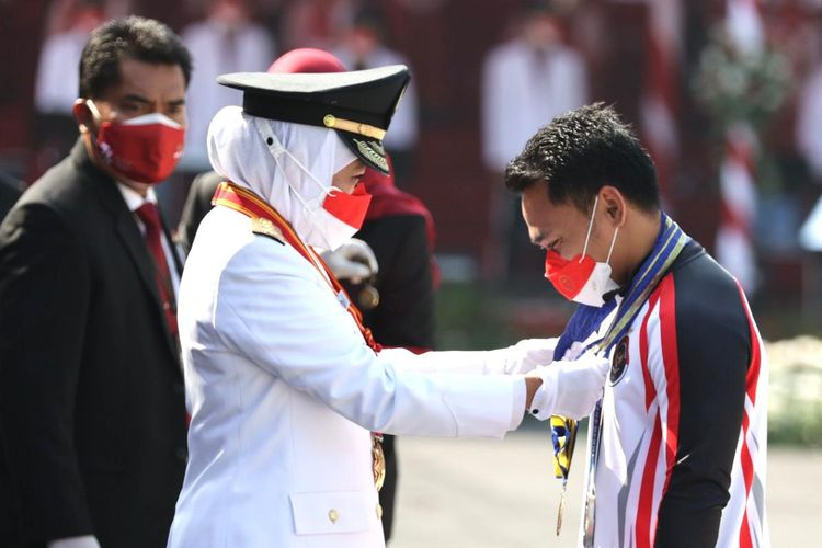 Gubernur Jawa Timur Khofifah Indar Parawansa memberikan lencana kepada lifter yang memperoleh medali perak untuk Indonesia pada Olimpiade Tokyo, Eko Yuli saat upacara memperingati HUT Kemerdekaan RI ke-76 di Gedung Grahadi Surabaya, Jawa Timur, Selasa (17/8/2021) pagi.