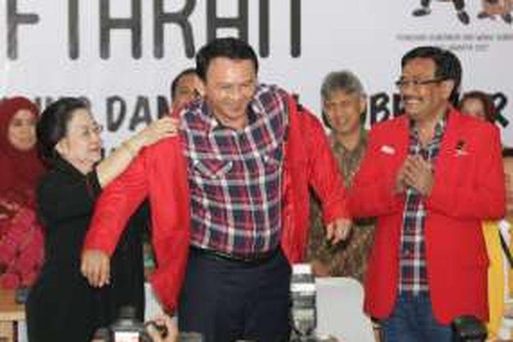 Basuki Tjahaja Purnama (Ahok) tersenyum saat dipakaikan jas berwarna merah oleh Ketua Umum PDI-P Megawati Soekarnoputri di KPU DKI Jakarta, Rabu (21/9/2016).