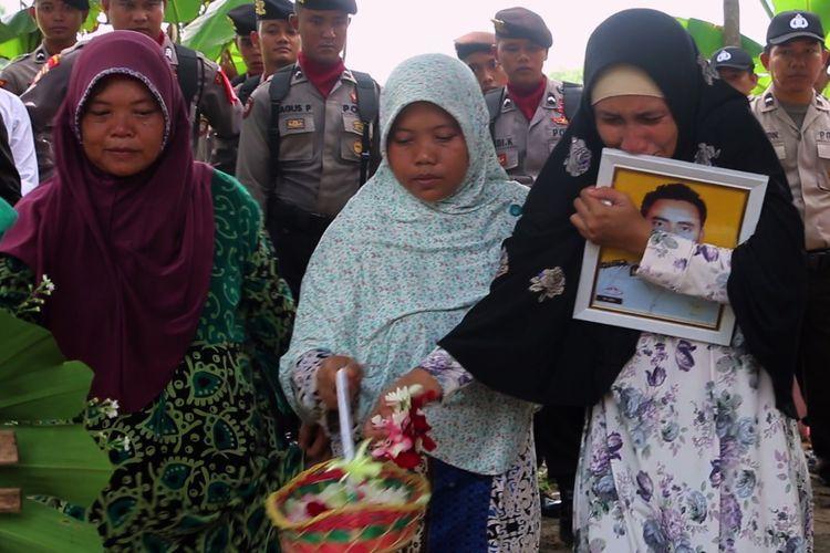 Sejumlah petugas Kepolisian Resor Indramayu Jawa Barat membawa jenazah Aipda Anumerta Mashadi menuju Tempat Pemakaman Umum (TPU) Desa Guwa Lor, Kecamatan Kaliwedi, Kabupaten Indramayu, Sabtu (20/4/2019). Aipda Anumerta Mashadi meninggal dunia karena kecelakaan saat mengamankan proses pemilu 2019.